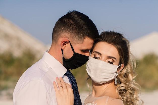 彼らの結婚式の日の検疫中に公園で医療マスクを歩いている若い愛情のあるカップル。