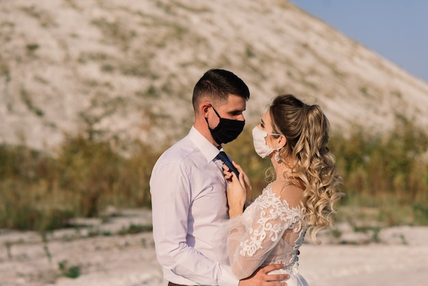 Young loving couple walking in medical masks in the park during quarantine on their wedding day.