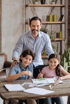水彩絵の具で絵を描いている間、後ろから彼の小さな子供たちを抱きしめている若い愛情深い父親、彼ら全員が正面で笑っている