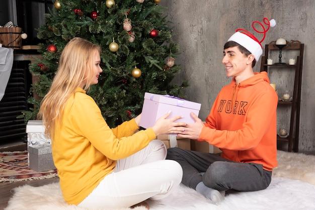 Regalo del regalo della giovane ragazza amorosa al suo ragazzo vicino all'albero di natale.