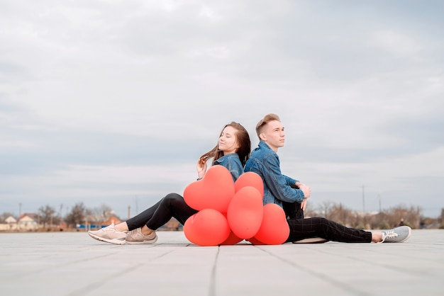 Young loving smiling couple sitting back to back in the street holding a pile of red balloons spending time together