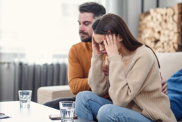 カウンセラー、フリースペースとの心理療法セッション中に落ち込んでいる夫をサポートする愛情のある若い妻