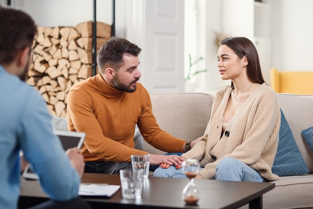 Young loving wife supporting her depressed husband during psychotherapy session with counselor, free space