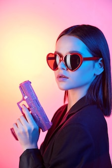 Young luxurious brunette woman in heart-shaped sunglasses and black jacket holding violet plastic gun