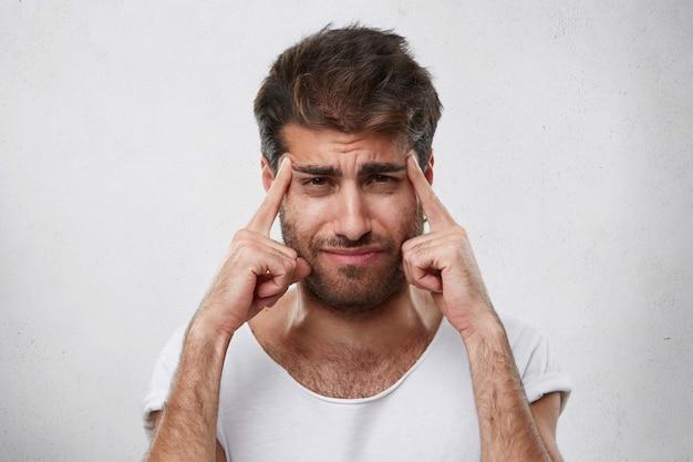 Giovane uomo macho con barba folta e acconciatura alla moda che tiene le dita sulle tempie cercando di concentrarsi o avere un'idea di qualcosa. bel ragazzo che sembra confuso mentre dimentica qualcosa di importante