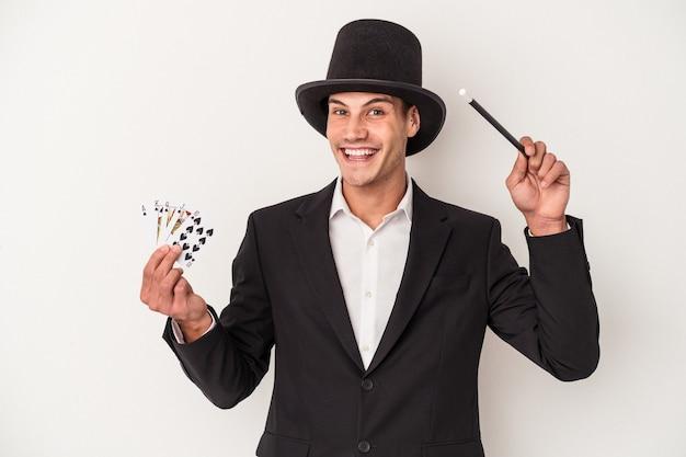 마술 카드와 지팡이를 들고 젊은 마술사 백인 남자 흰색 배경에 고립
