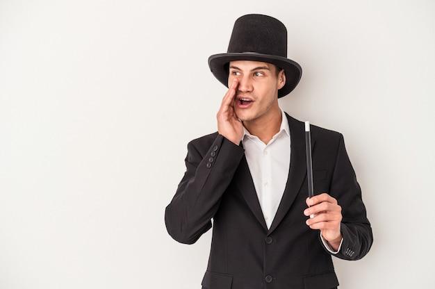 白い背景で隔離の杖を保持している若いマジシャン白人男性は、秘密のホットブレーキニュースを言って脇を見ています