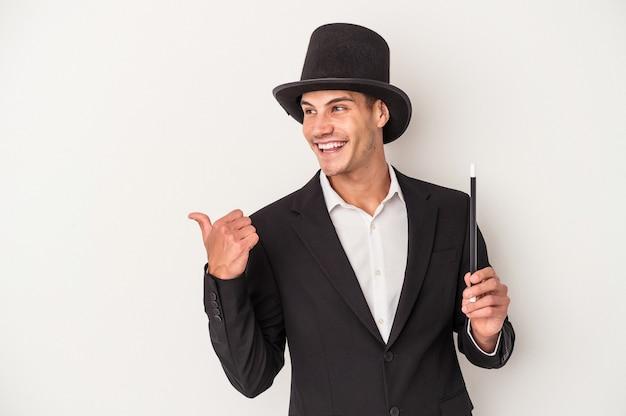 白い背景のポイントで隔離された杖を持って親指の指を離して、笑ってのんきな若いマジシャン白人男性。
