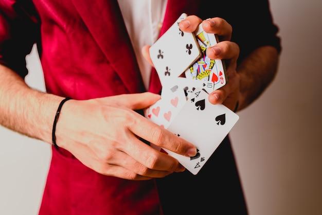 카드 놀이의 갑판을 저글링하는 젊은 마술사.