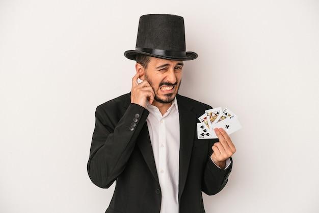手で耳を覆う白い背景で隔離の魔法のカードを保持している若い魔術師の男。