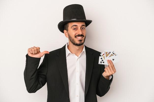 白い背景に分離された魔法のカードを持っている若い魔術師の男は、誇りと自信を持って、従うべき例を感じます。