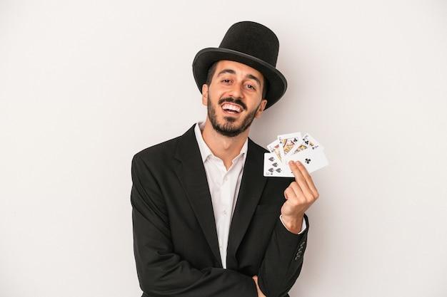 笑って楽しんでいる白い背景で隔離の魔法のカードを保持している若い魔術師の男。