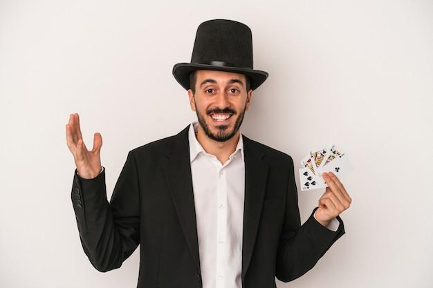 白い背景で隔離の魔法のカードを持っている若い魔術師の男は、嬉しい驚きを受け取り、興奮し、手を上げます。