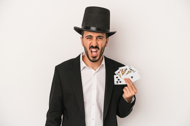 非常に怒って攻撃的に叫んで白い背景で隔離の魔法のカードを保持している若い魔術師の男。