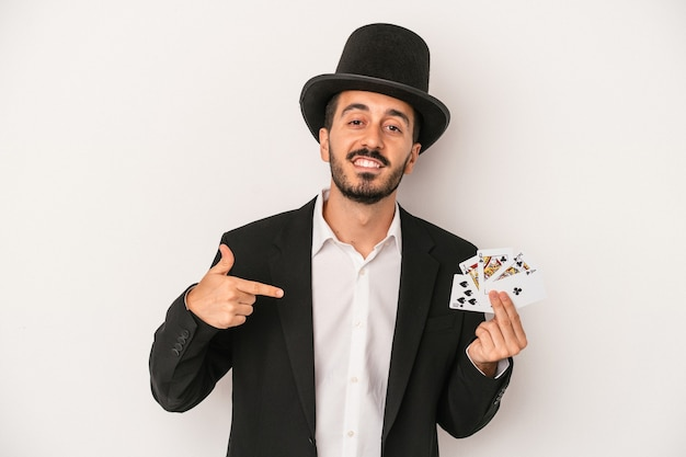 Young magician man holding a magic card isolated on white background person pointing by hand to a shirt copy space, proud and confident