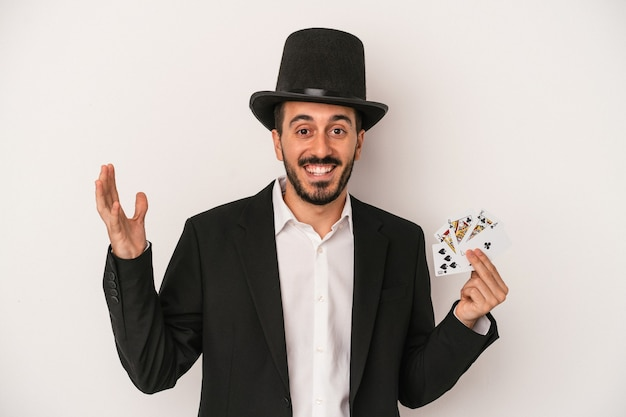 Young magician man holding a magic card isolated on white background receiving a pleasant surprise, excited and raising hands.