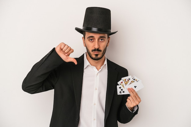 Young magician man holding a magic card isolated on white background showing a dislike gesture, thumbs down. disagreement concept.