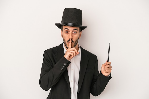秘密を保持するか、沈黙を求めて白い背景で隔離の杖を保持している若い魔術師の男。