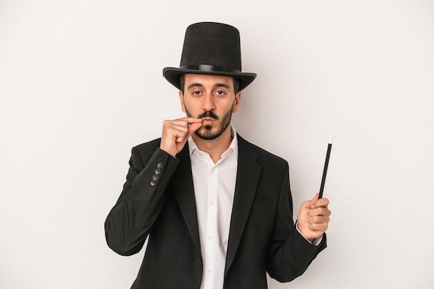 秘密を保持している唇に指で白い背景に分離された杖を保持している若い魔術師の男。