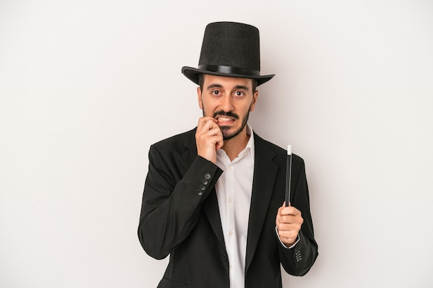 Young magician man holding wand isolated on white background biting fingernails, nervous and very anxious.