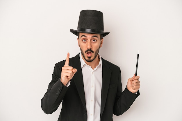 Young magician man holding wand isolated on white background having an idea, inspiration concept.