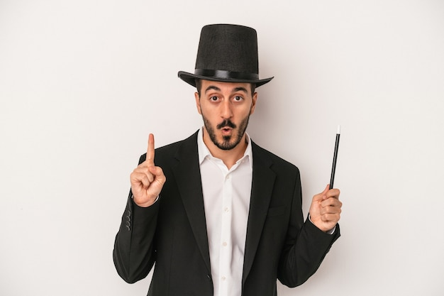 Young magician man holding wand isolated on white background having some great idea, concept of creativity.