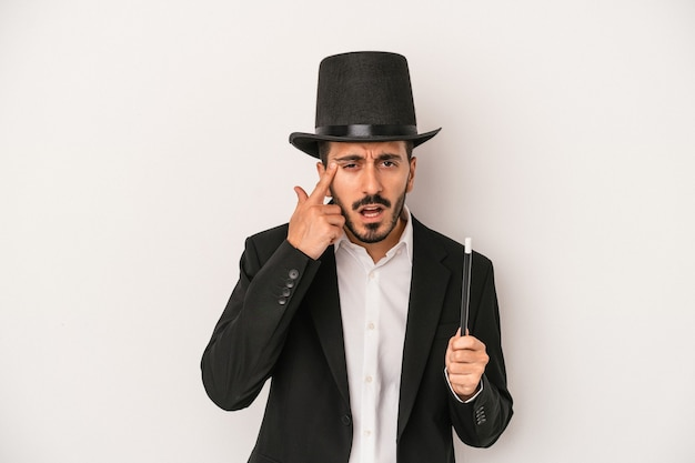Young magician man holding wand isolated on white background showing a disappointment gesture with forefinger.