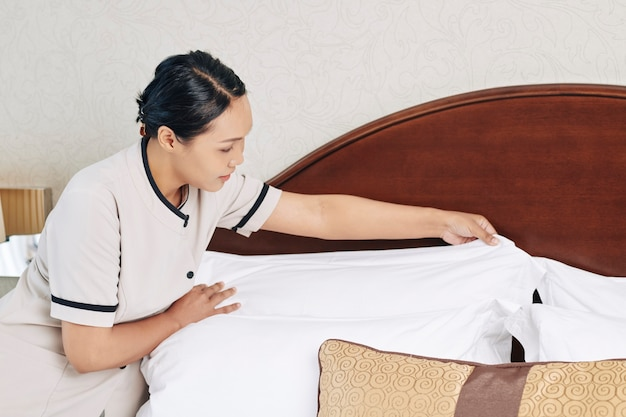 ベッドシーツを交換し、次のゲストのためにホテルの部屋を準備する若いメイド