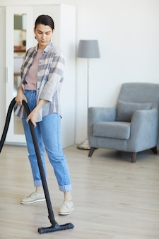 Young maid cleaning the house using vacuum cleaner
