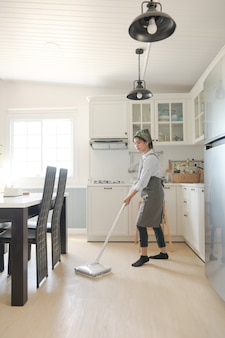 A young maid cleaning the house with a mop there is a kitchen backdrop
