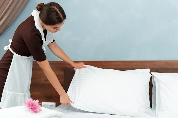 Young maid making bed in hotel room