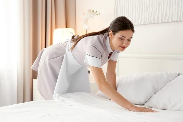 가벼운 호텔 방에서 침대를 만드는 젊은 하녀