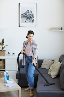 Young maid using vacuum cleaner in the living room she vacuuming dust from the sofa
