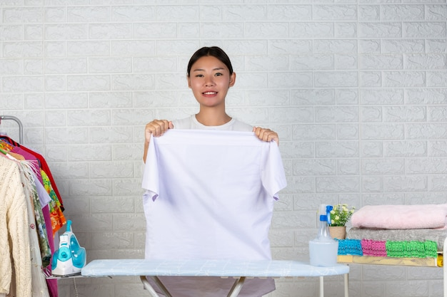 A young maid who is preparing a shirt on her ironing board with a white brick .