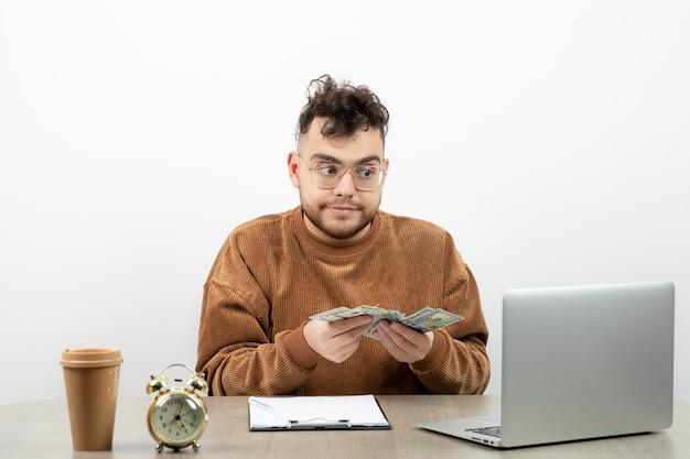 彼の机に座って現金を見せている若い男性会計士。