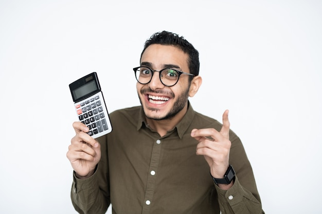 Young male accountant or student in eyeglasses looking at you with toothy smile while holding calculator and pointing upwards