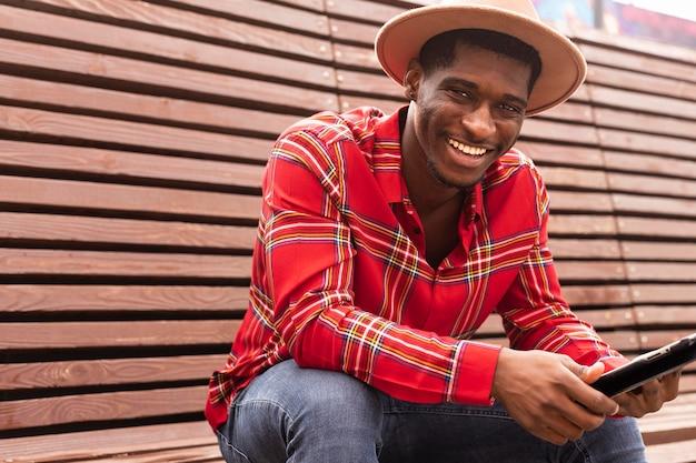 Giovane maschio adulto che tiene una tavoletta digitale e sorrisi