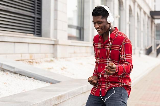 Молодой взрослый мужчина слушает музыку и танцует