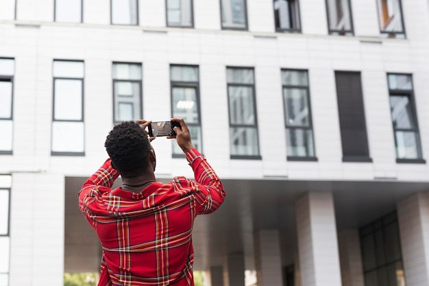 Young male adult taking pictures of a building