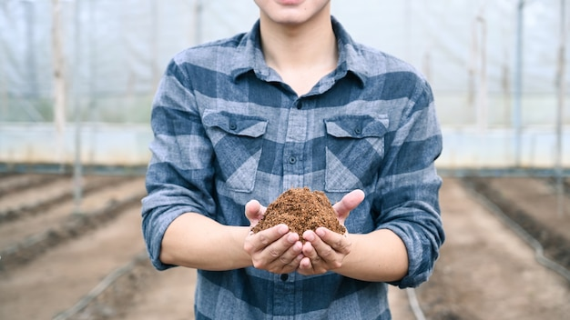 Young male agronomist holding soil and examining quality of fertile agricultural field.