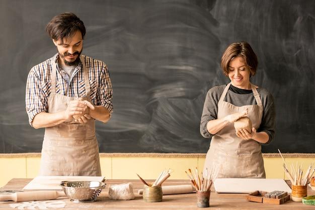 ワークショップでテーブルのそばに立っている間混練用の粘土を準備する作業服の若い男性と女性の職人