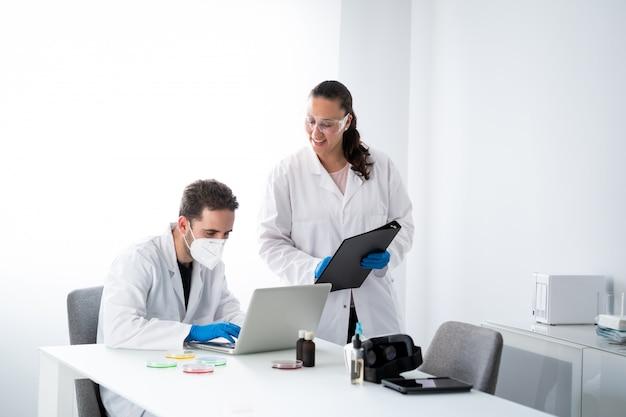 Молодые мужчины и женщины работают в современной научной лаборатории биологии и биотехнологии.