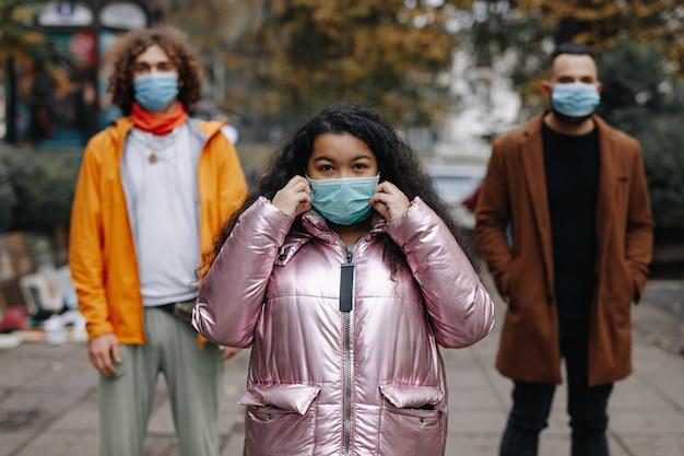 通りの距離に立っている医療保護マスクの若い男性と女性。コロナウイルスとパンデミック時間の概念。