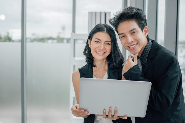 Молодые мужчины и женщины с помощью ноутбука и глядя на камеру.