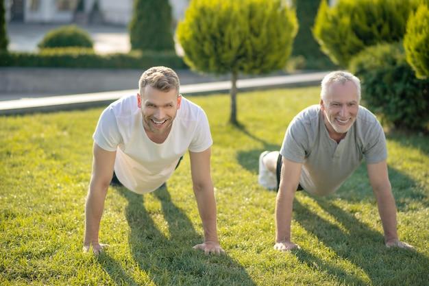 Молодой мужчина и седой мужчина делают отжимания на траве
