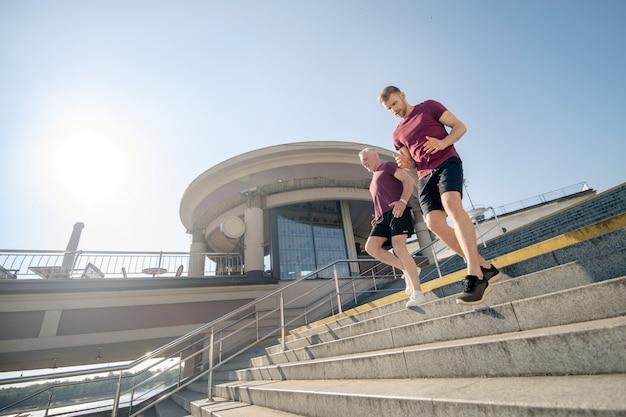 若い男性と灰色の髪の男性運動、階段を下りて