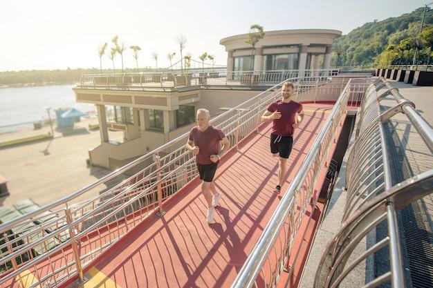 橋を渡って一緒に走っている若い男性と成熟した白髪の男性