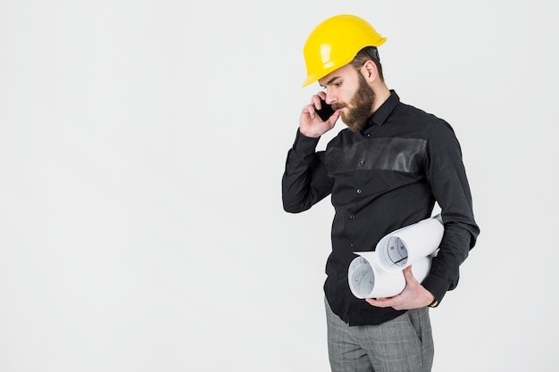 Young male architect holding blue prints talking on mobile phone