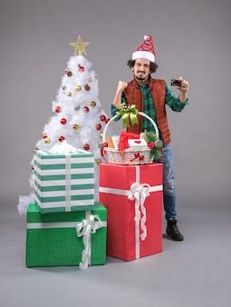 Молодой мужчина вокруг рождественских подарков на сером