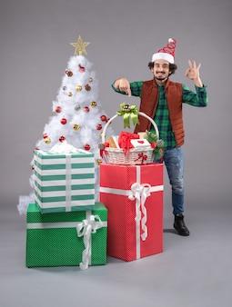 Молодой мужчина вокруг разных подарков на сером